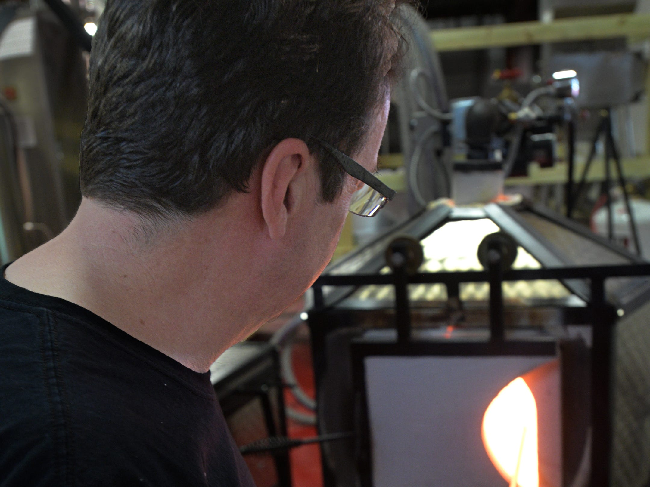 Sanctuary Glass Studio co-owner Eric Hess heats glass before shaping it.