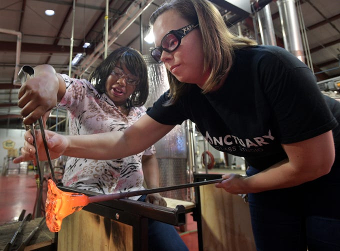 Sanctuary Glass Studio co-owner Michelle Pennington (right) teaches Tiana Kennell how to work with molten glass.