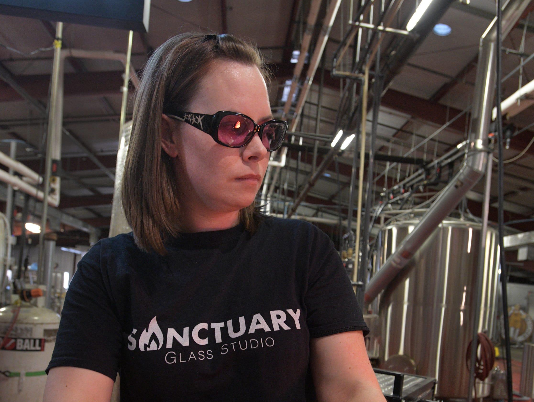 Sanctuary Glass Studio co-owner Michelle Pennington works with molten glass.