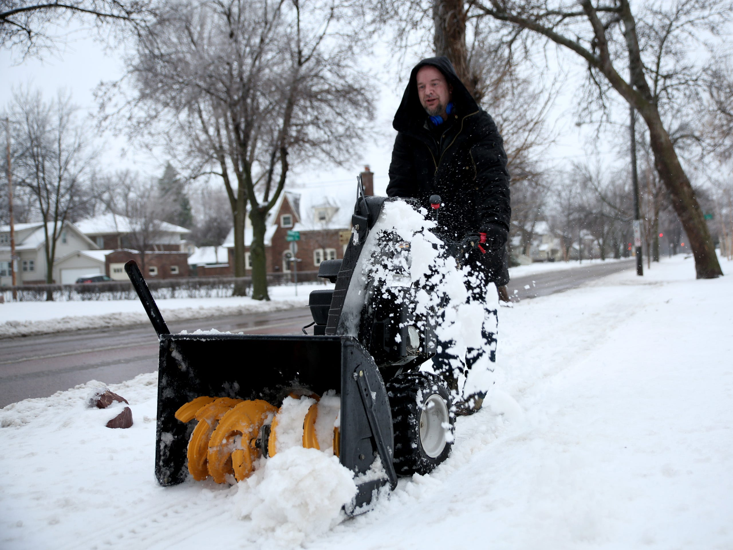 Kyle Stettnichs snow blows his neighborhood block on Thursday, April 11. He said he was clearing his neighbors' snow because the mix of ice, sleet, rain and snow was too heavy for them to shovel.