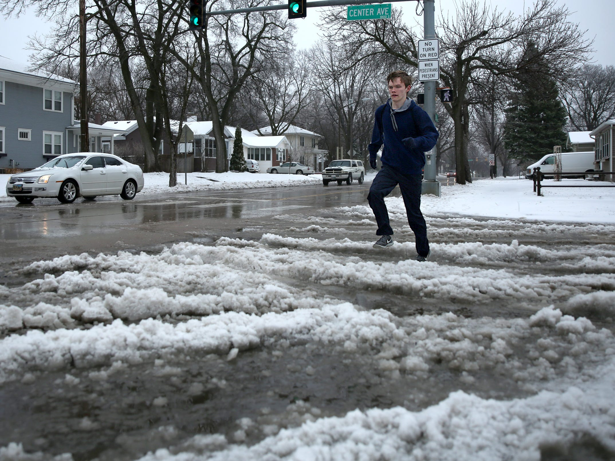 Adam Monson avoids slush as he runs along 26th Street on Thursday, April 11. School was canceled for the 15-year-old so he decided to fill up his time with exercise.