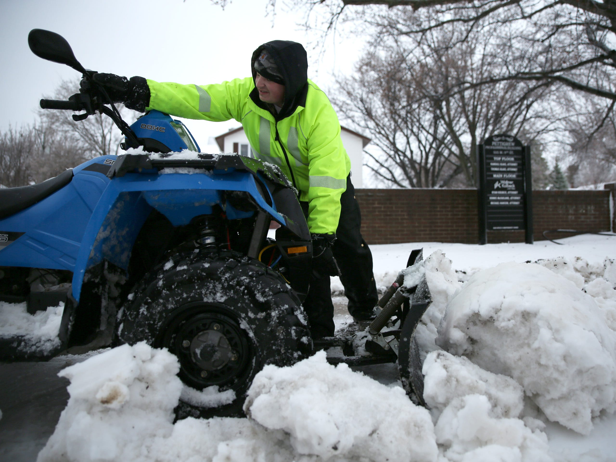 Dan Preston, owner of Mr. Plow, fixes his four-wheeler while plowing snow on a client's property on Spring Avenue Thursday, April 11.