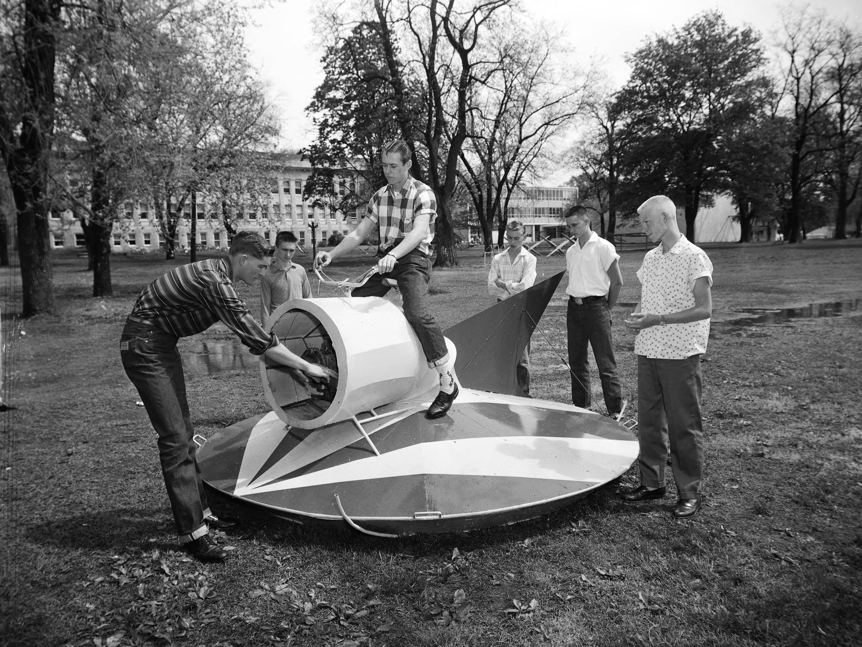 Two Norwood High School seniors built this flying saucer for the tenth annual Southwest Missouri State College Student Craftsman's Fair. Seated at the handlebar controls is Jack Hylton while Edwin Derrin spins the propeller. Others pictured are Wayne Honsinger, Gary Strohm, Jack Barnett, and Vic Harris. Published in the Leader & Press on April 29, 1960.
