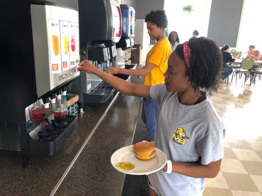 Mary Baldwin sophomore Alice Wardy gets some juice for lunch Tuesday in the school's dining hall.
