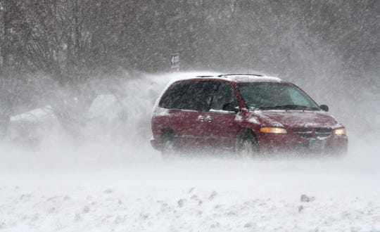 Heavy snow and sleet driven by high winds swirls around traffic on Stearns Country Road 75 Thursday, April 11, west of St. Cloud.