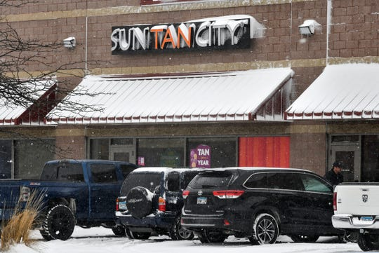 Snow falls in front of Sun Tan City Thursday, April 11, in St. Cloud.