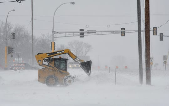 Snow is cleared from a parking lot as more snow continues to fall Thursday, April 11, west of St. Cloud.