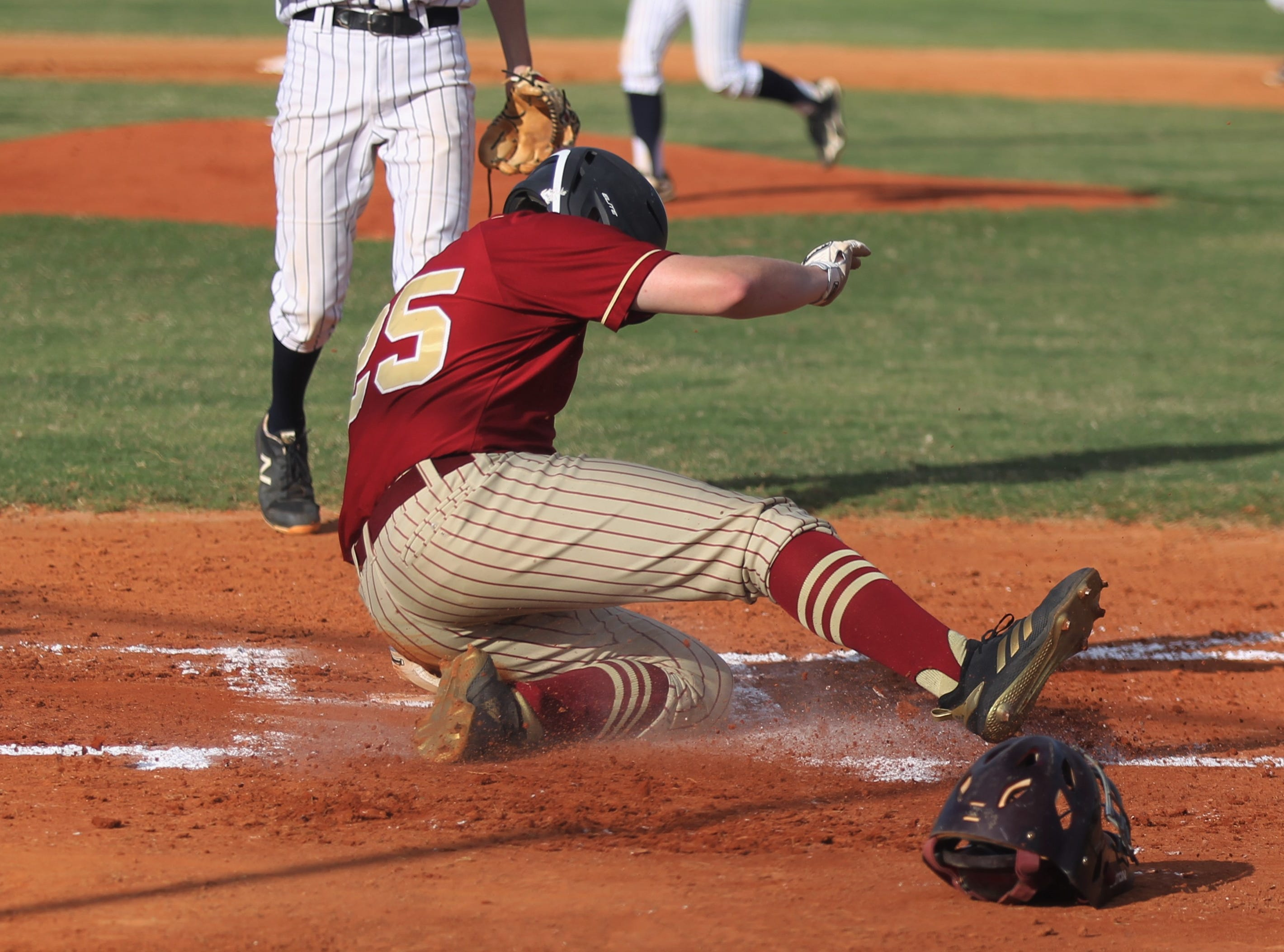 Florida High senior Brady Blackburn slides in for a run as Florida High won 11-3 on the road at St. John Paul II on Tuesday, April 3, 2010.
