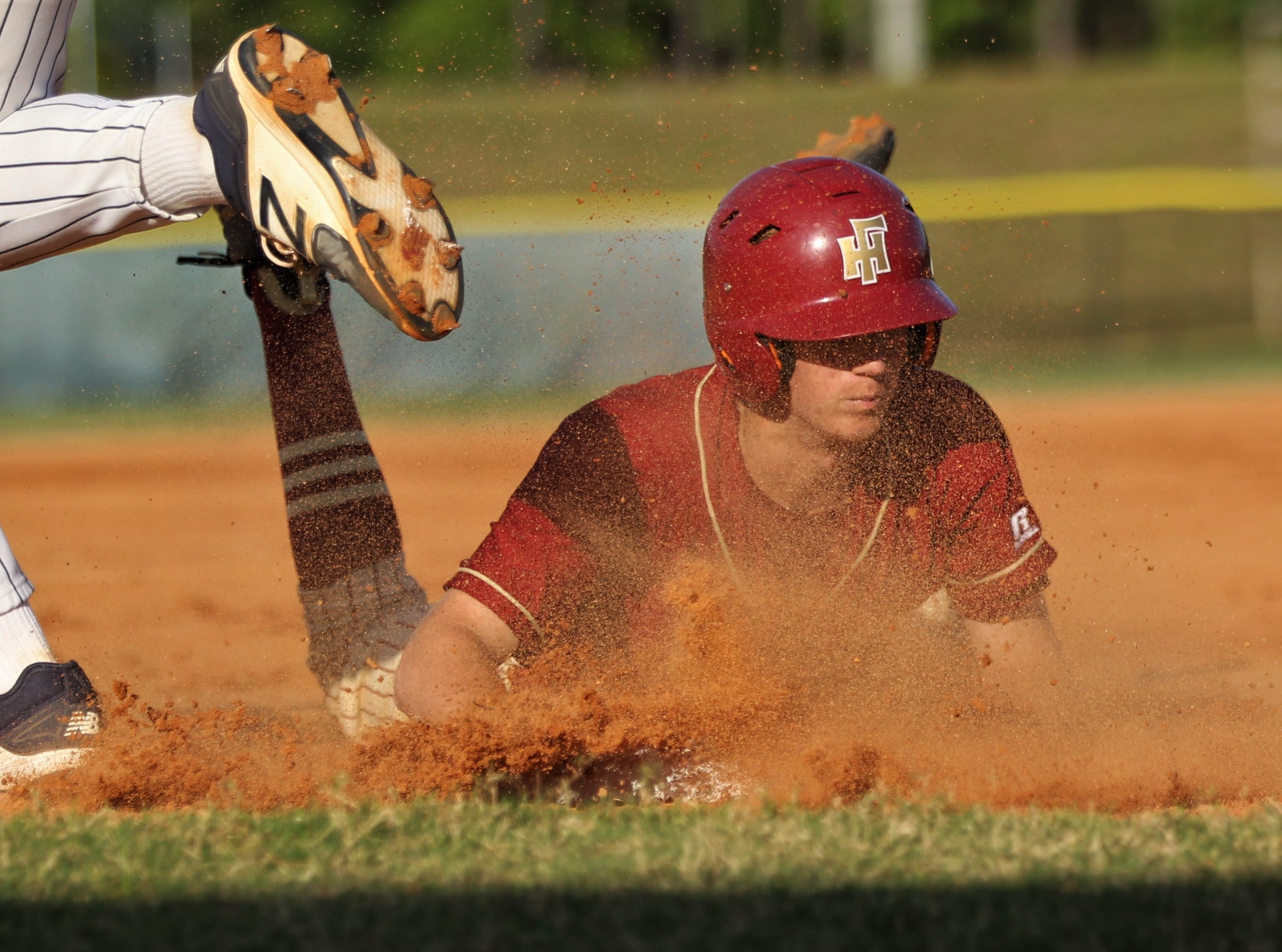 Florida High junior A.J. Thorp slides safely into third base as Florida High won 11-3 on the road at St. John Paul II on Tuesday, April 3, 2010.