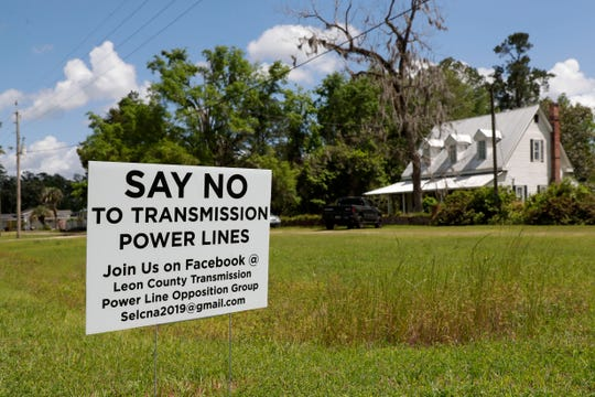 "A ""Say No To Transmission Power Line"" silently protests in Wacissa, Fla. New transmission line poles would be put in place a little more than 40 feet from a family's front door."