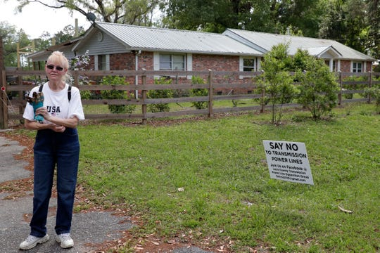 "Carole McMullen, a concerned Wacissa homeowner, stands in front of her home with one of the many ""Say No To Transmission Power Line"" signs that line her yard."