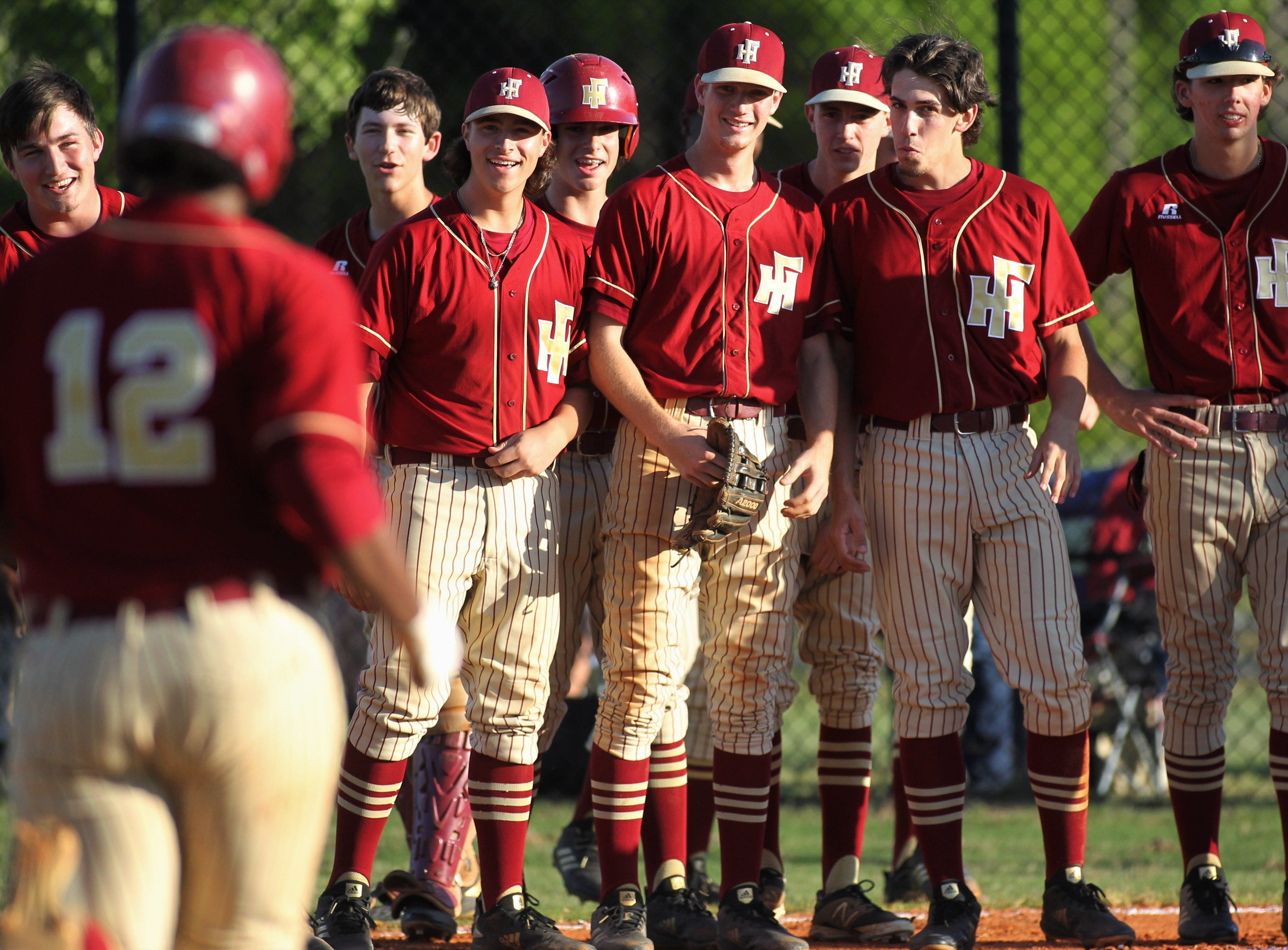 Florida High's baseball team waits to greet Malachi Burke after a home run as Florida High won 11-3 on the road at St. John Paul II on Tuesday, April 3, 2010.