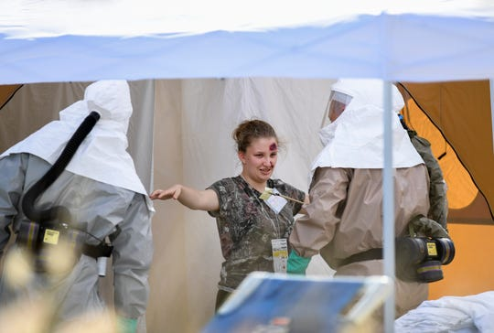 """Sadie Peters, 18, a junior at St. Lucie West Centennial High School, plays the part of a victim going through decontamination and being treated by the Hospital Emergency Response Team, (HERT), at the Cleveland Clinic Tradition Hospital in Port St. Lucie on Thursday, April 11, 2019, during full-scale disaster preparedness exercises. """"It helps to save a life,"""" Peters said. More than 150 high school students are participating, playing the roll of victims, during the exercise. Cleveland Clinic Martin Health hospitals, along with the Central Florida Disaster Medical Coalition, are participating in the exercises."""