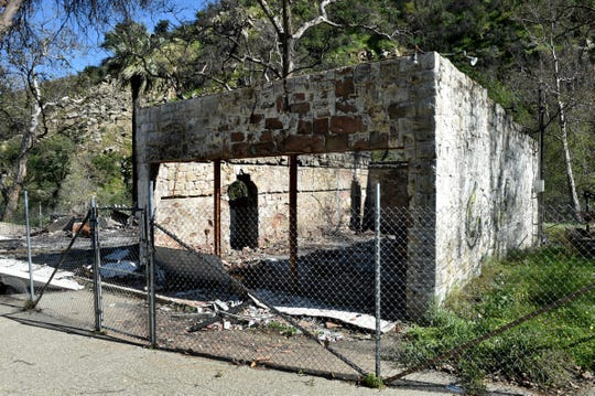 A former Matilija Hot Springs post office building, with walls made of stone, is fenced off. The Thomas fire swept through the area in late 2017. The floor of the building is currently covered in ash and possibly asbestos. The Ventura County Watershed Protection District, which owns the historic site, wants to level the property.