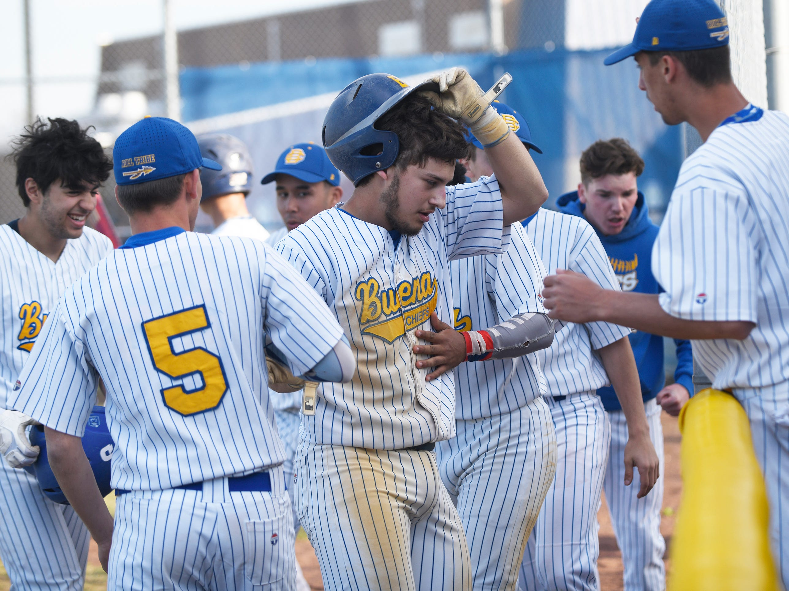 Buena catcher Jake Guglielmi is congratulated by the team after scoring a run against Cedar Creek on Wednesday, April 10, 2019.