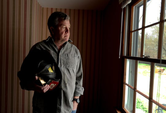 Retired NYFD Fire Marshall John Coyle holds the helmet he wore on Sept. 11, 2001. Coyle, photographed at his home in South Salem April 11, 2019, was standing near the base of the south tower of the World Trade Center when it fell. As he ran in the other direction, his only thought was that he was sure he was going to die. Almost eighteen years later, Coyle suffers from numerous 9/11 related illnesses. He and other first responders are now finding out the the victim's compensation fund is running out of money and will not fully compensate him and many others for the illnesses they contracted due to their time spent at Ground Zero.