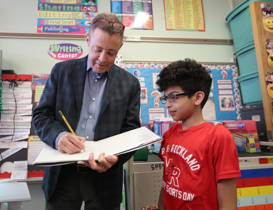 Jerry Cahill, left, signs an autograph for a third grade in the classroom of Jen LaBier Stony Point Elementary School in Stony Point on Thursday, April 11, 2019.