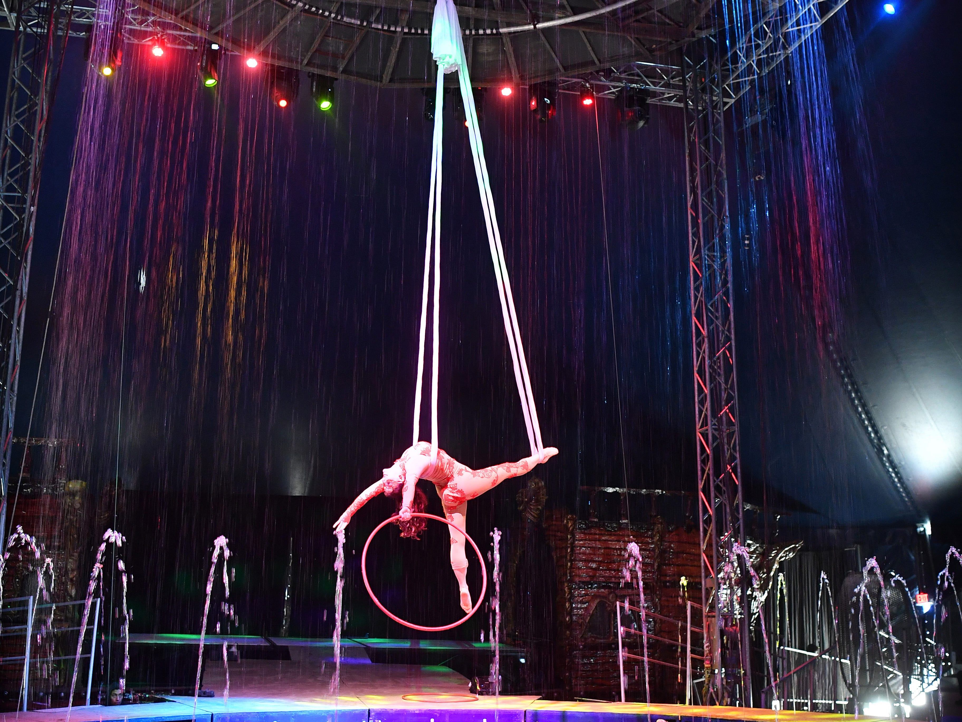 Elena Stefanova performs a dramatic aerial swing act as a cable lifts her high within a curtain a water during a performance with the Cirque Italia water circus Thursday.