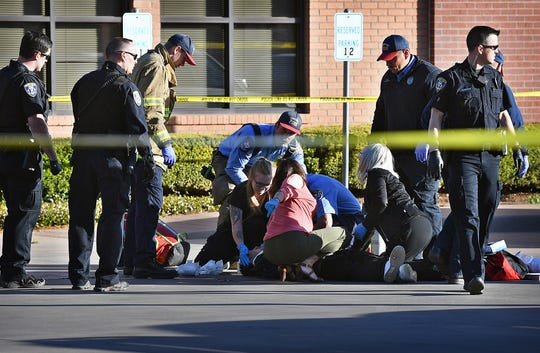 Emergency medical personnel care for a man shot Thursday morning near the intersection of Martin Luther King Jr. Blvd and Third Street. The armed subject was shot by police during a foot pursuit.