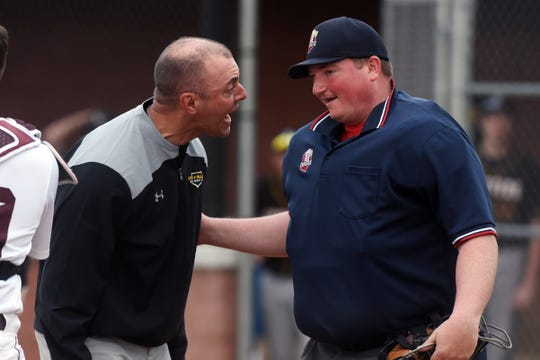 Tri-Valley coach Kevin Yoder argues a game-ending call with home plate umpire Grant Hutcheson following the Scotties' 6-4 loss to John Glenn on Wednesday in New Concord.