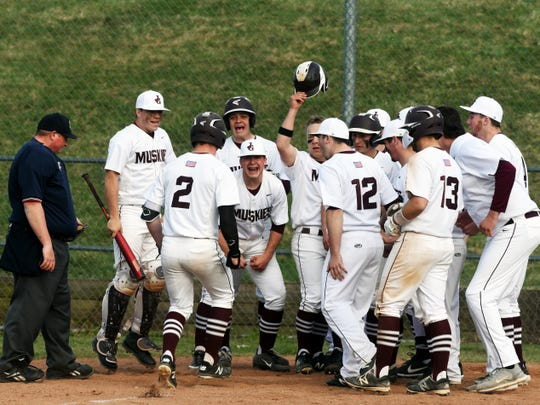 John Glenn players meet Ben Larson at the plate after he hit a three-run homer in the fifth inning on Tuesday during a 6-4 win against Tri-Valley on Wednesday in New Concord.