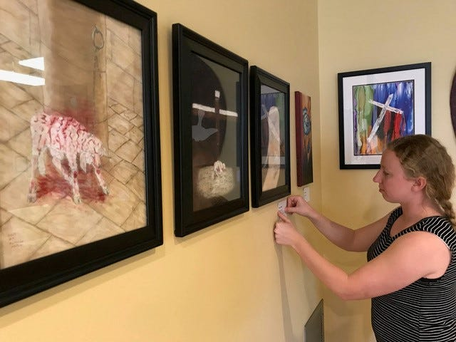 Hillary Hendricks hangs artwork and labels for the In the Waiting art show at Immanuel Church on display during Holy Week.