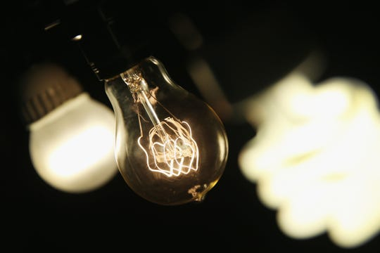 An incandescent light bulb between energy-efficient ones.