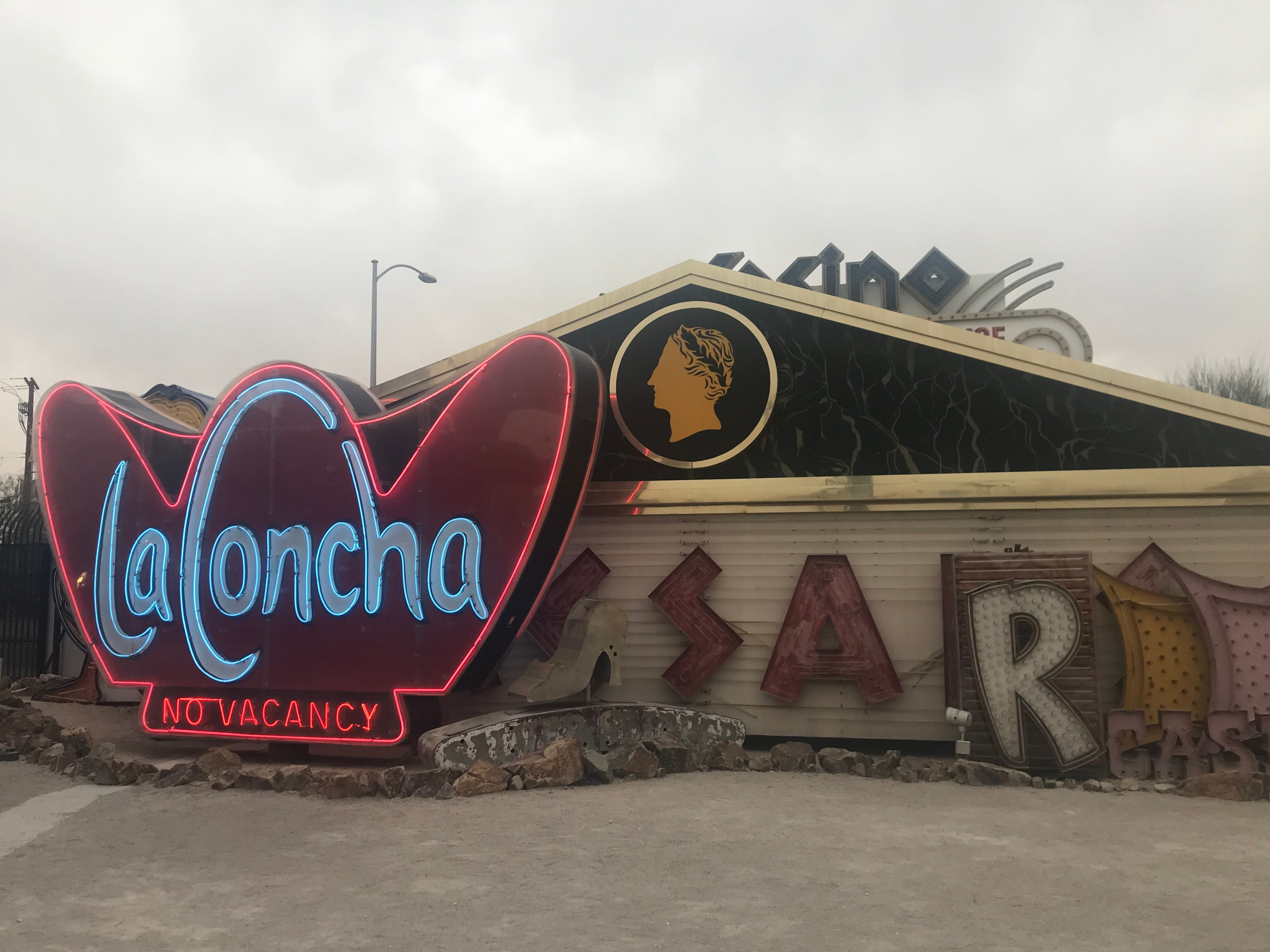 A lit-up sign from the La Concha Motel sits against an old Caesars Palace sign at the Neon Museum.