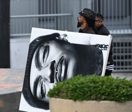 A large image of  Nipsey Hussle, is carried into the Staples Center for a memorial service in Los Angeles.