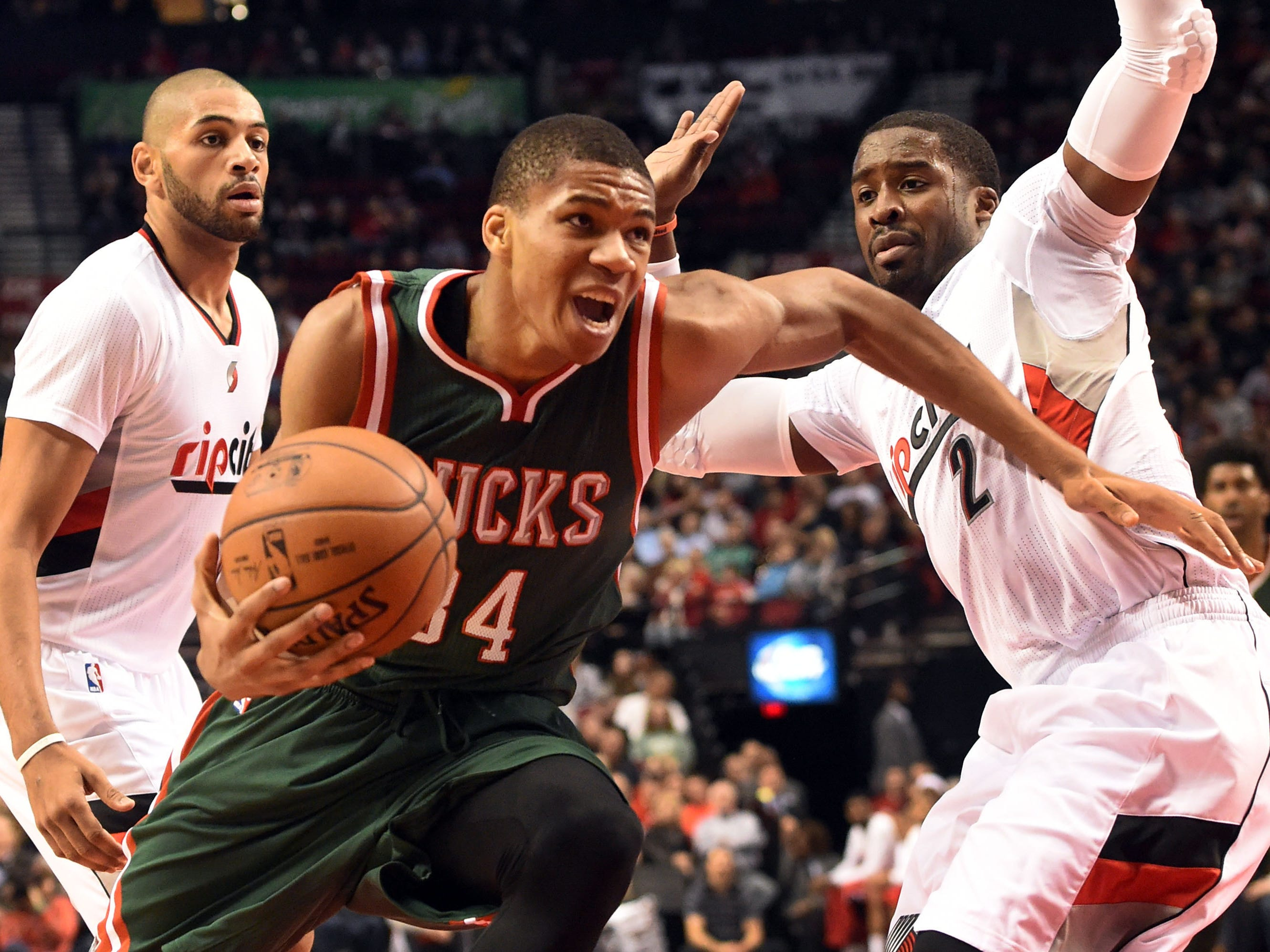 Antetokounmpo drives to the basket on Nicolas Batum and Wesley Matthews during a 2014 game.