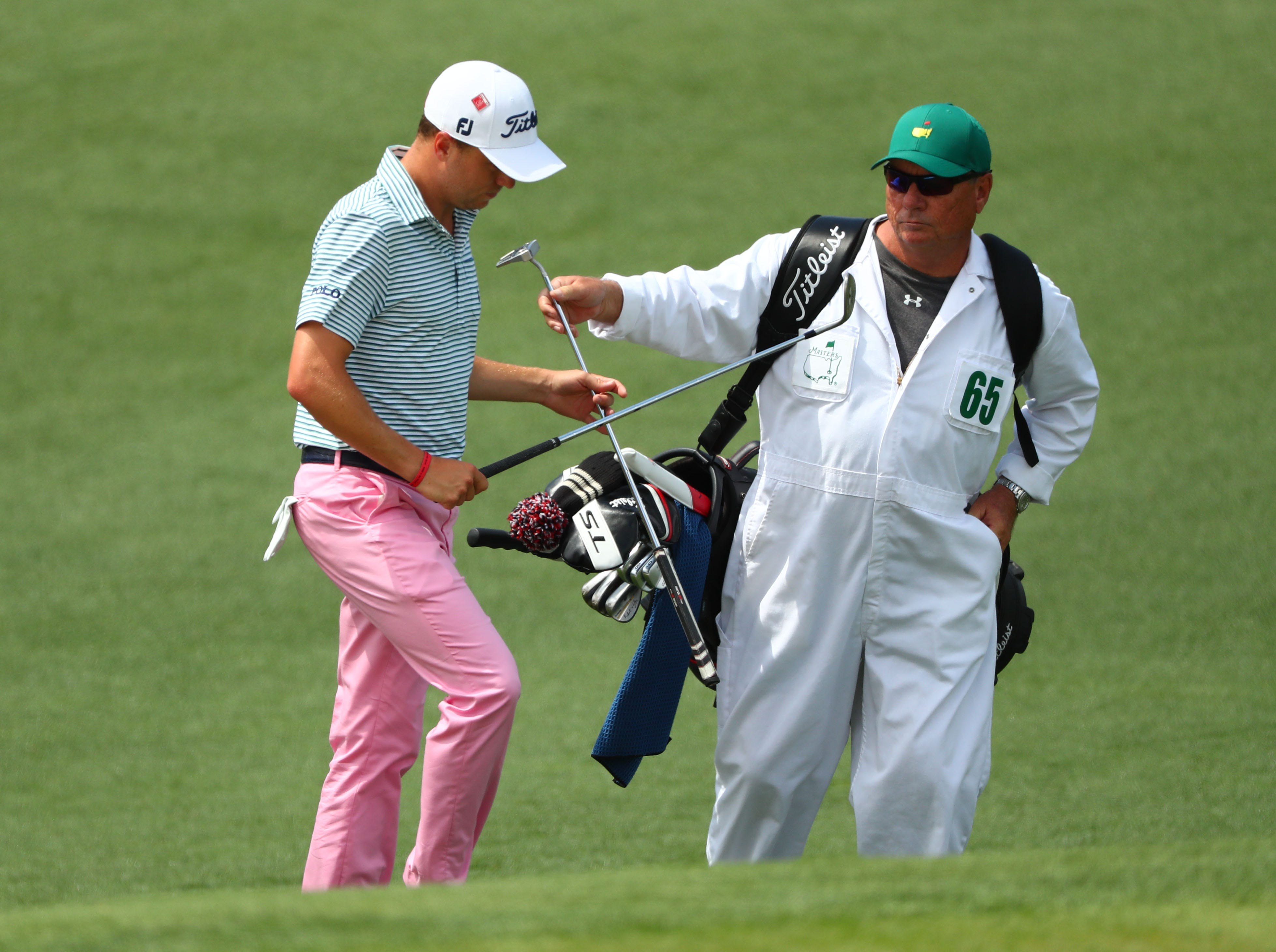 Justin Thomas exchanges clubs with caddie Jimmy Johnson on the second green during the first round of the Masters.