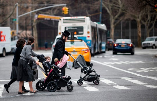 A Jewish man and two woman pushes strollers as they cross a street in a Jewish quarter in Williamsburg Brooklyn on April 9, 2019 in New York City. - New York Mayor Bill de Blasio declared a public health emergency across part of Brooklyn, ordering all residents receive the measles vaccine in a bid to contain an outbreak of the disease. (Photo by Johannes EISELE / AFP)JOHANNES EISELE/AFP/Getty Images