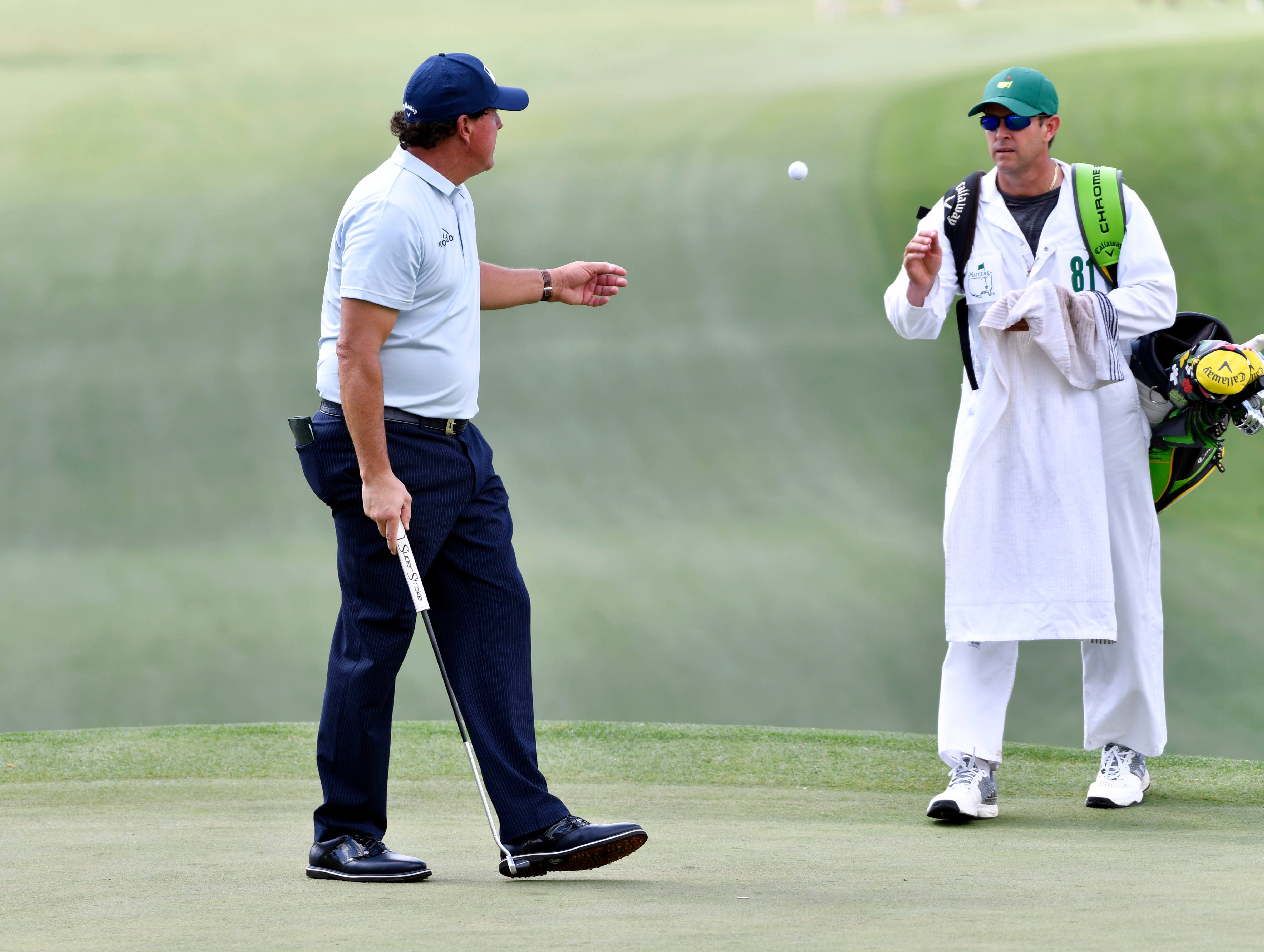 Phil Mickelson tosses his ball to caddie Tim Mickelson on the seventh green during the first round of the Masters.