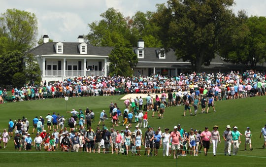 Patrons walk the course during the first round of the Masters at Augusta National Golf Club.