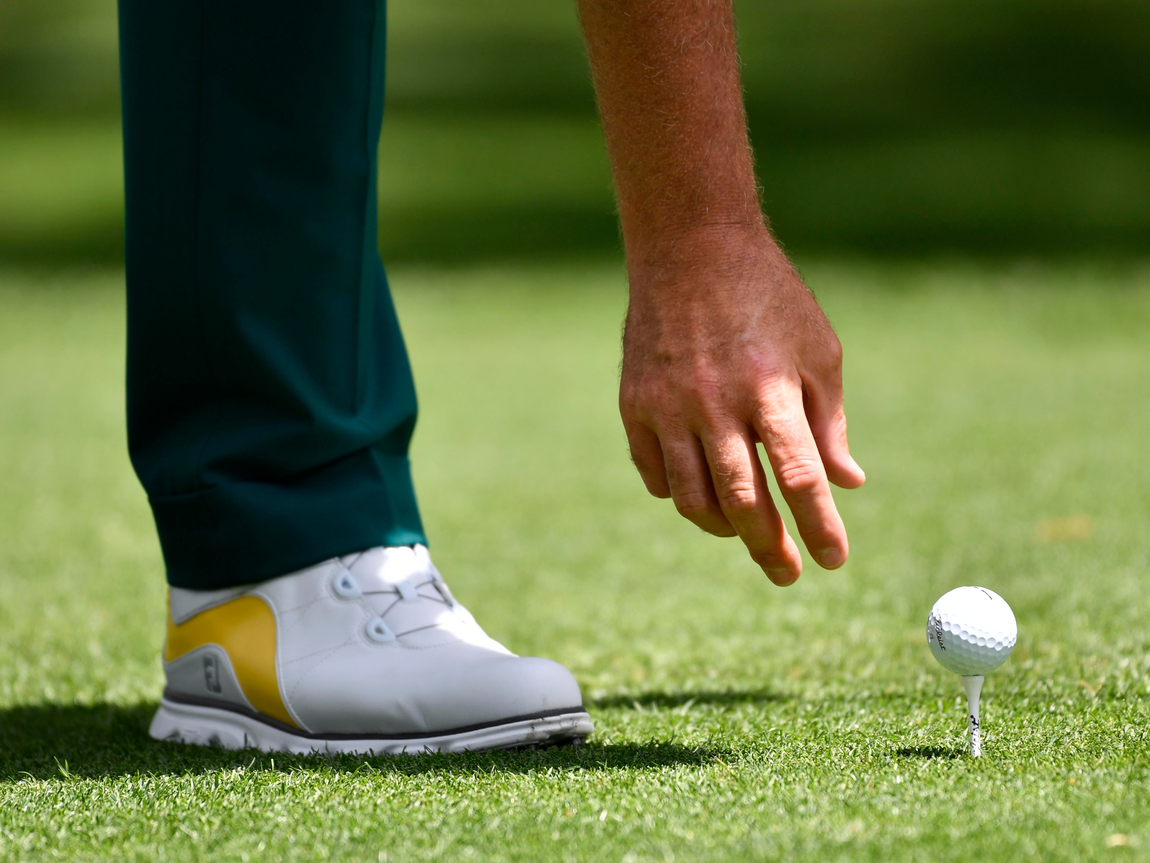 Ian Poulter places his ball on the tee during the first round of the Masters.
