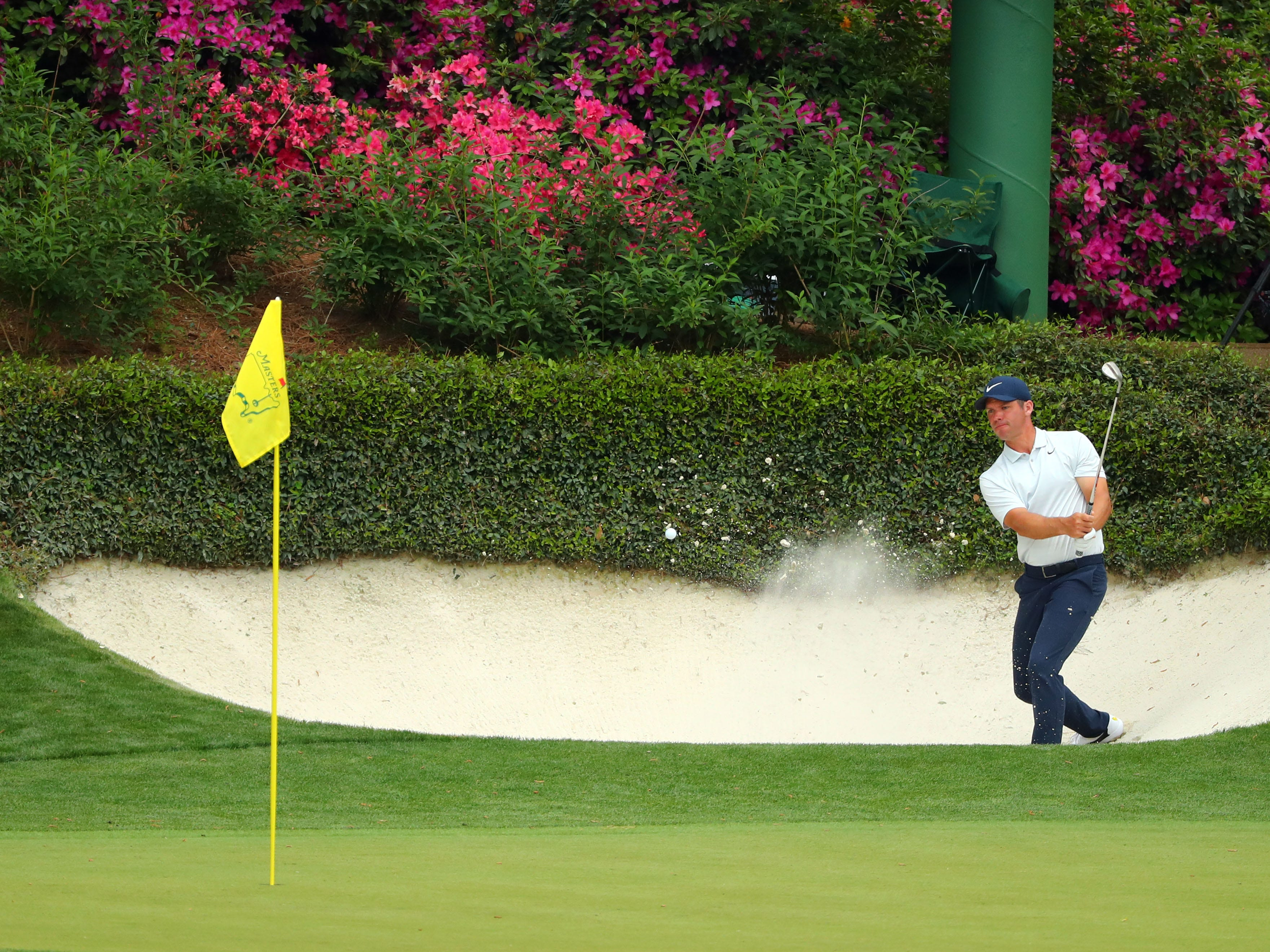 Paul Casey hits out of a bunker on the 12th hole during the first round of the Masters.