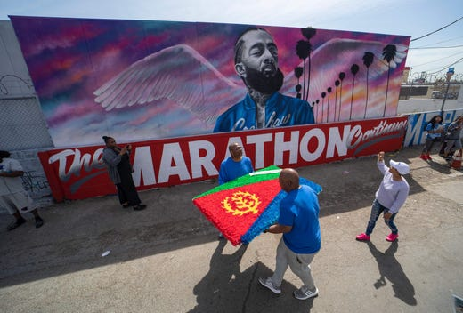 Fans and community members gather along the procession route for Nipsey Hussle following his memorial at the Staples Center in Los Angeles, April 11, 2019.