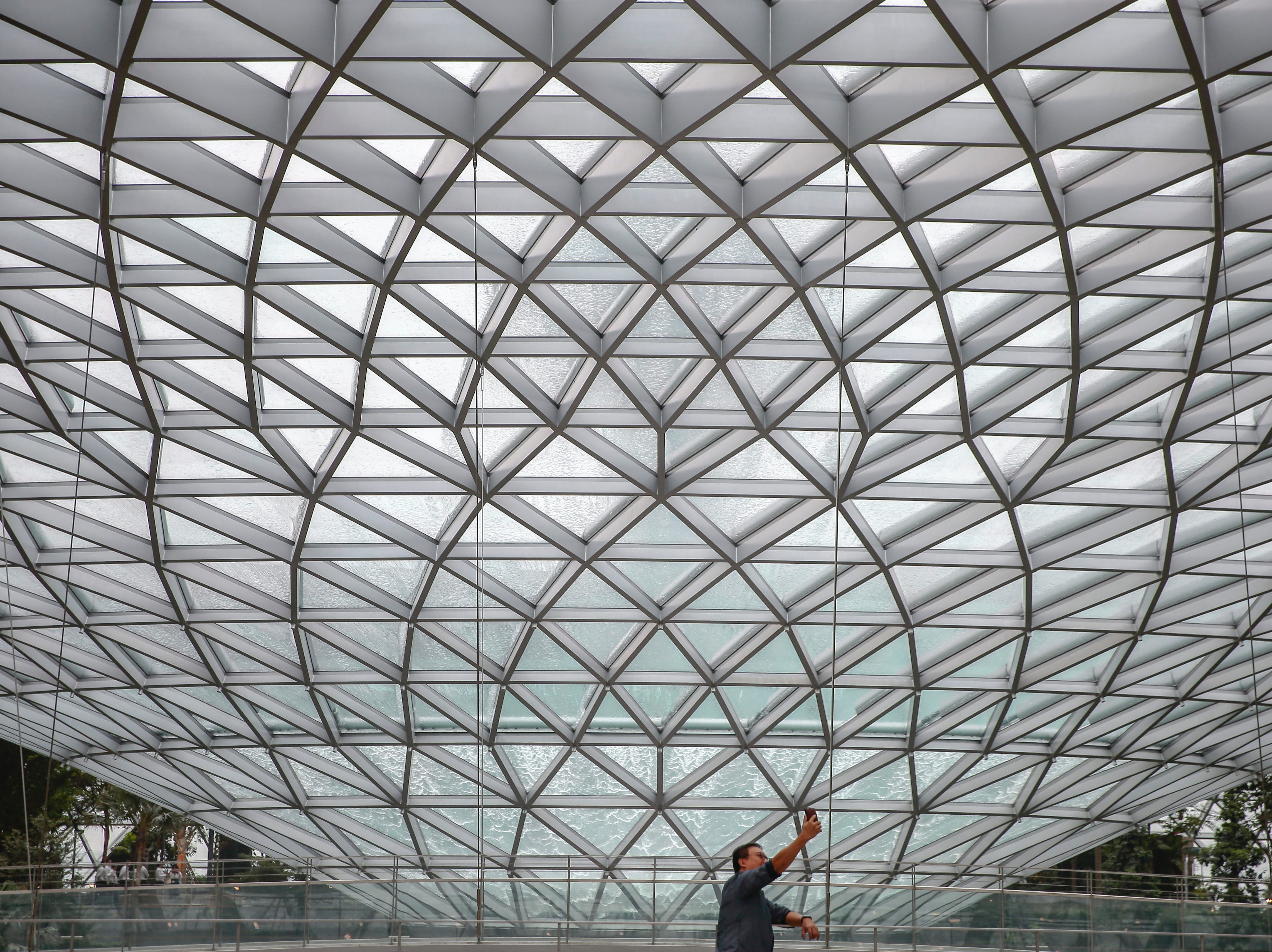 A man takes a selfie underneath the facade of Jewel Changi. The airport is expected to have between 40 and 50 million visitors each year.