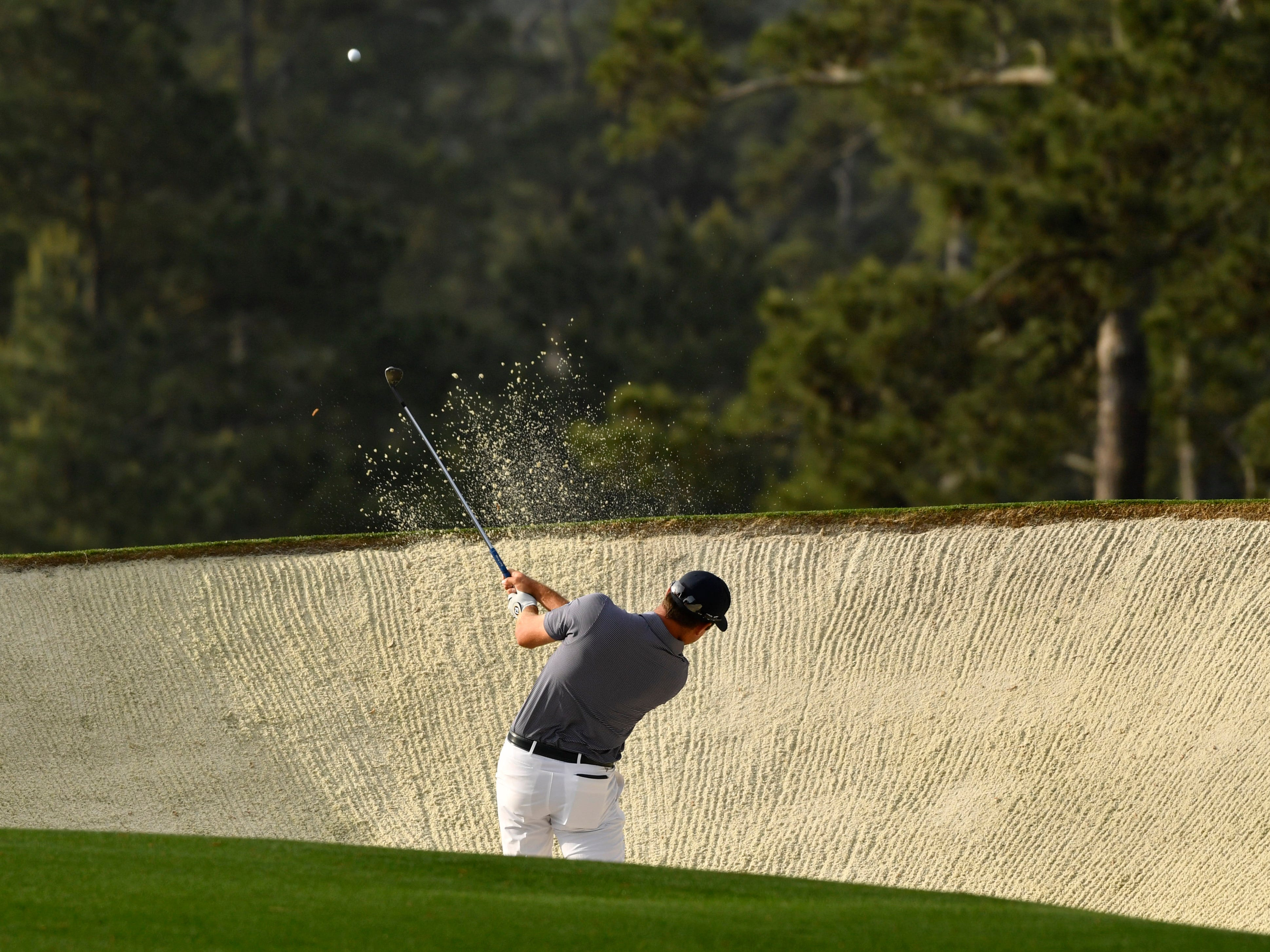 Corey Conners hits out of a bunker during the first round of the Masters.