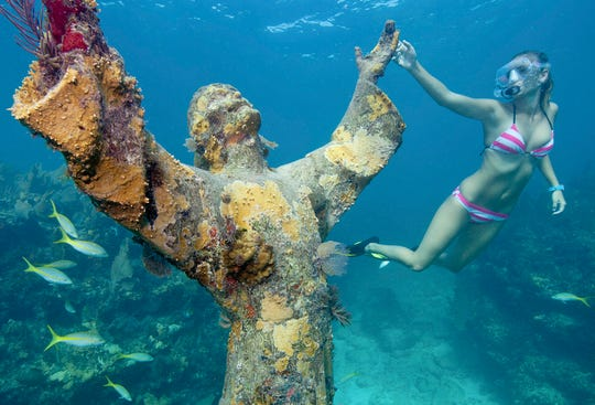 Christ of the Deep stands nearly 9 feet in height, surrounded by gardens of coral and teeming sea life.