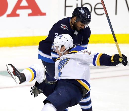 First round: Winnipeg Jets defenseman Dustin Byfuglien checks St. Louis Blues center Oskar Sundqvist in the second period.