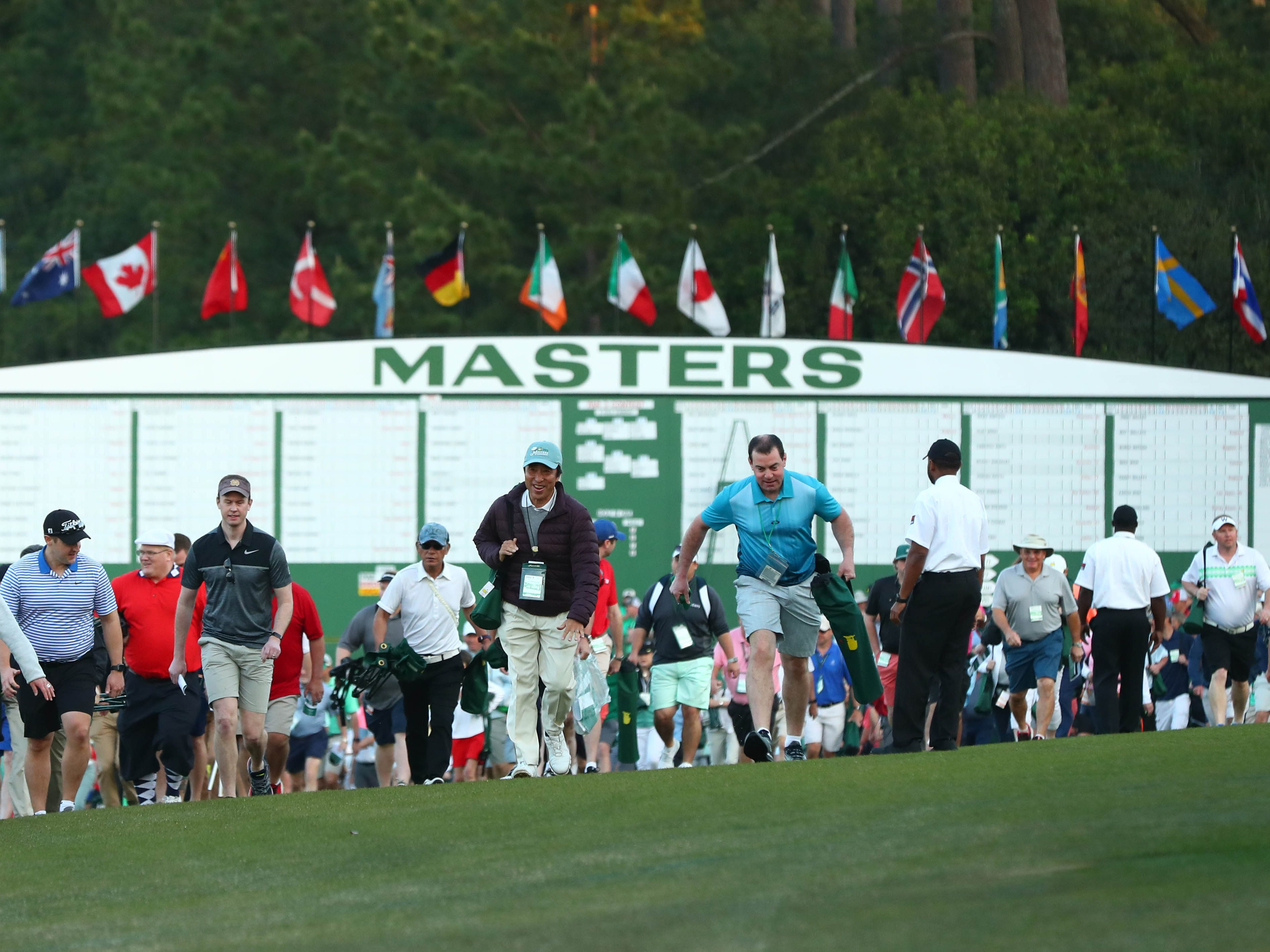 Patrons make their way onto the course during the first round of the Masters.
