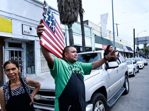 Raul Rico watches as the funeral procession for Nipsey Hustle drives past his business on Vermont Ave. in Los Angeles.