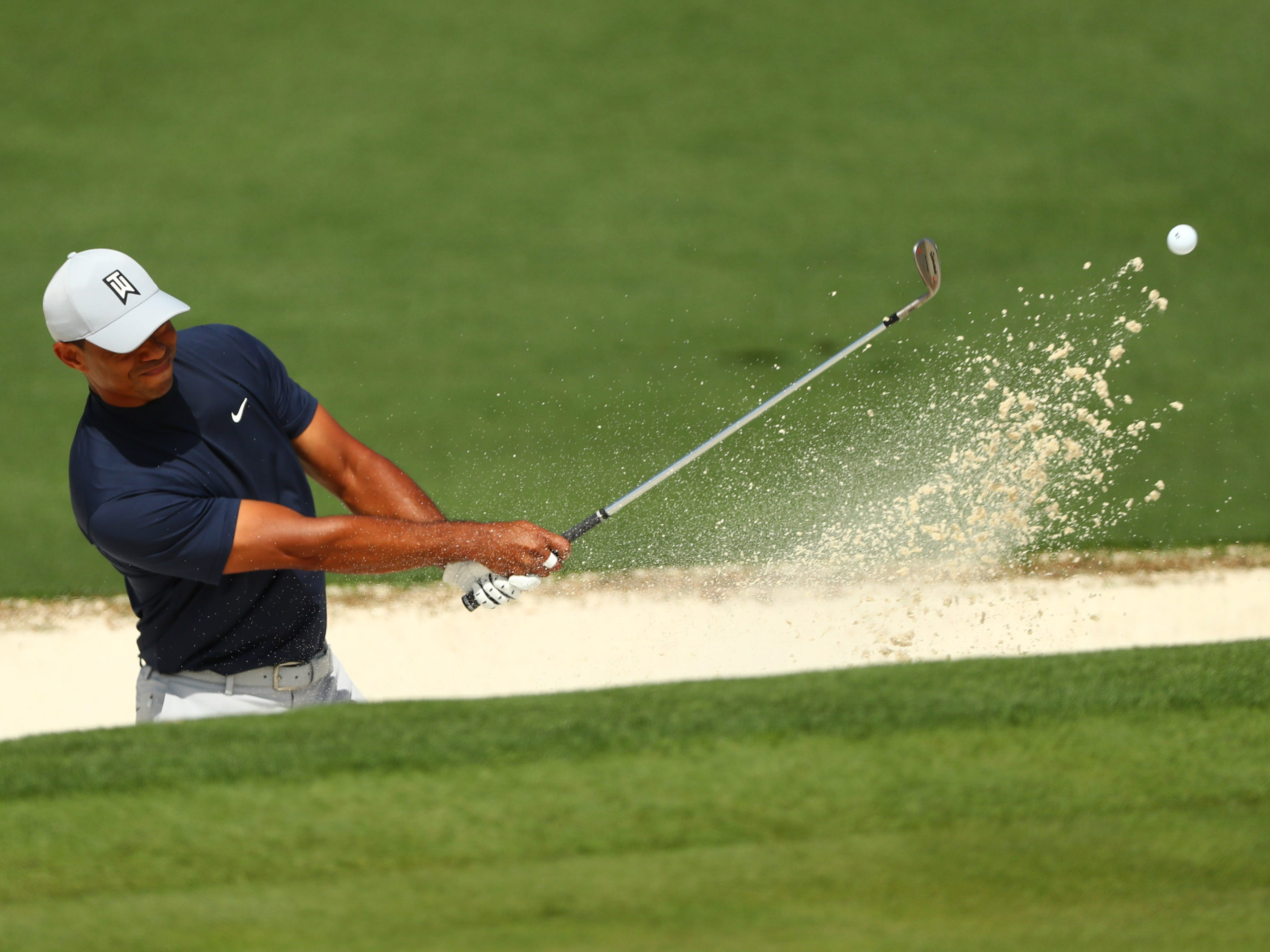 Tiger Woods hits out of a bunker during the first round of the Masters.
