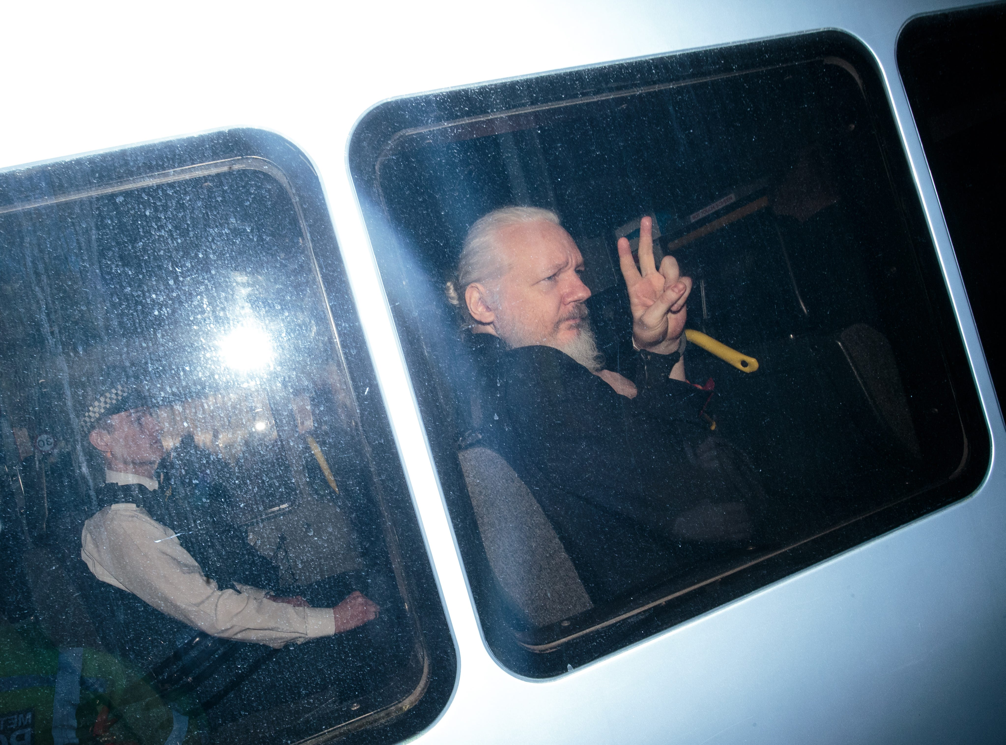 Julian Assange gestures to the media from a police vehicle on his arrival at court on April 11, 2019 in London, England.