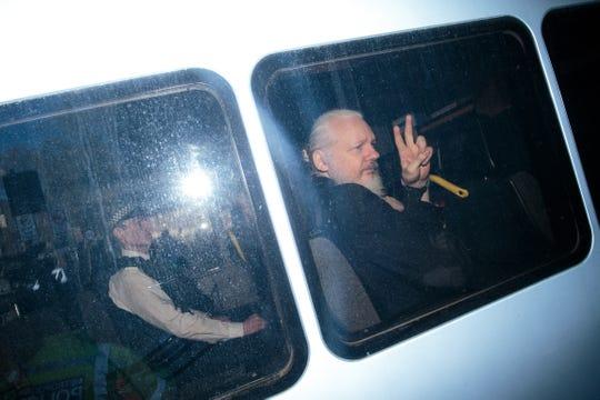 Julián Assange saluda a la prensa tras ser transportado por la policía de Londres a una corte.