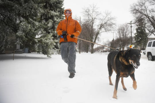 David Heinold walks his dog Max, a German Shepard lab mix, through the snow Thursday, April 11, 2019 in Sioux Falls, S.D. Heinold said Max is a very energetic dog and needs to be walked everyday despite what the weather is like. He said Max loves the snow so he isn't phased by the weather.