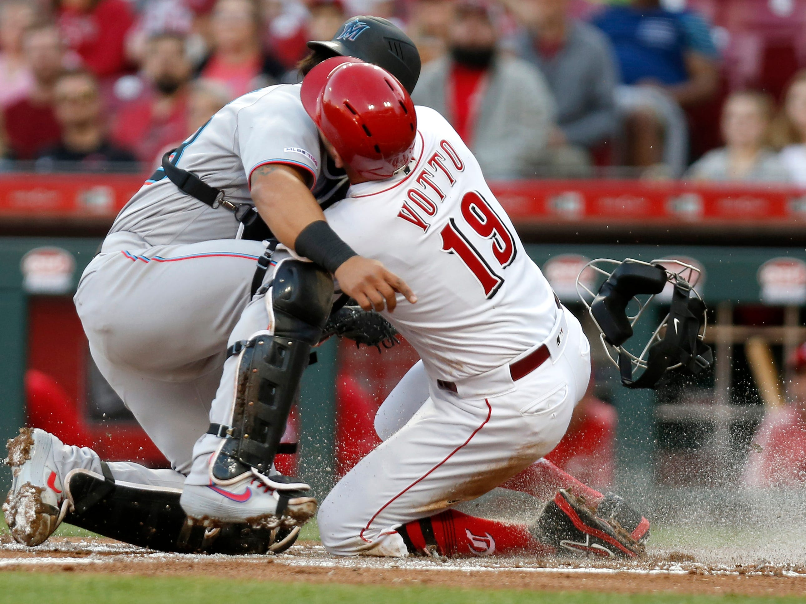 April 10: The Cincinnati Reds' Joey Votto (19) is tagged out at home plate by Miami Marlins catcher Jorge Alfaro during the first inning at Great American Ball Park. The Reds won the game, 2-1.