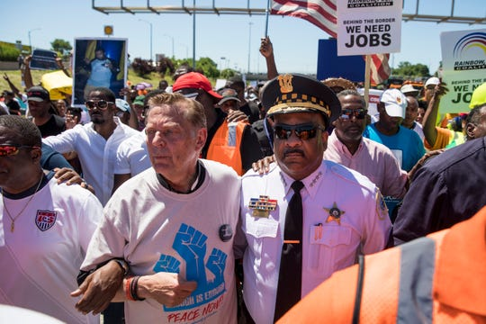 Rev. Michael Pfleger and Chicago Police Supt. Eddie Johnson march arm-in-arm alongside protesters who poured into the inbound lanes of Interstate 94 known as the Dan Ryan Expressway Saturday, July 7, 2018 in Chicago.