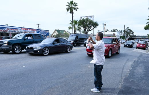 A man shoots video on his cellphone of Nipsey Hussle's funeral procession following a memorial service at the Staples Center in Los Angeles.